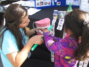 Stephanie Rebollar, oral health outreach and volunteer coordinator for Smile Mobile 2 provides oral hygiene education to a young community member.