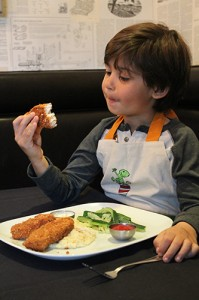 Diego enjoys the swordfish sticks he just make with his mom.