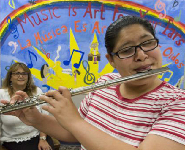 Stephanie Diaz, who has been attending OCCTAC for the last 14 years, plays the flute with Founder Dr. Ana Jimenez-Hami looking on.
